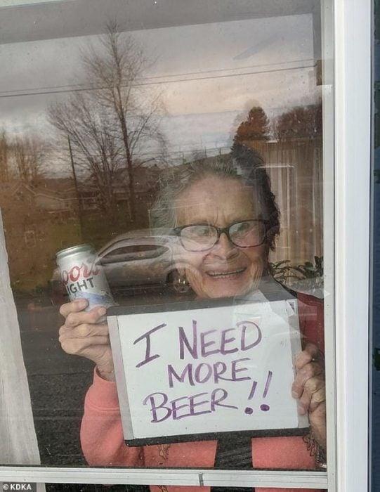 Abuelita en cuarentena sostiene letrero pidiendo más cerveza