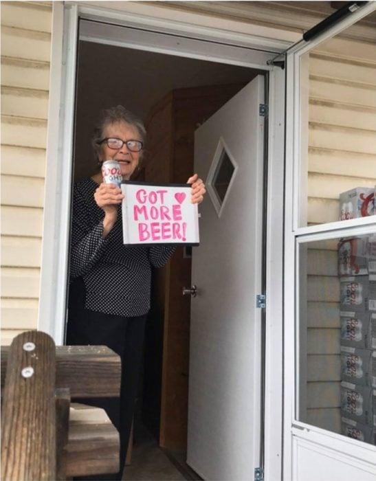 Abuelita en cuarentena sostiene letrero que asegura ya tiene cerveza suficiente
