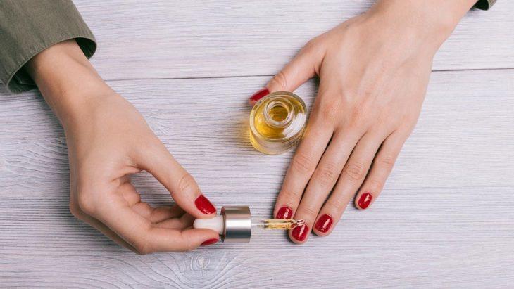 Chica aplícando aceite de cutícula