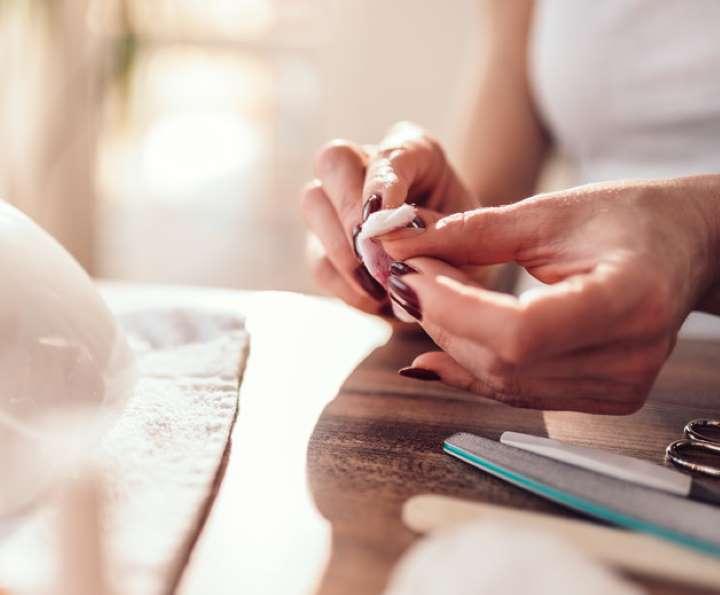Chica aplicando algodón con acetona sobre sus uñas