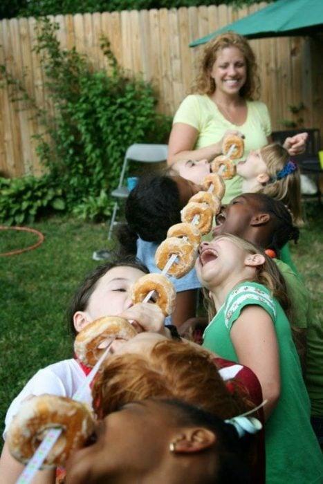 Niños comiendo donas desde una cuerda