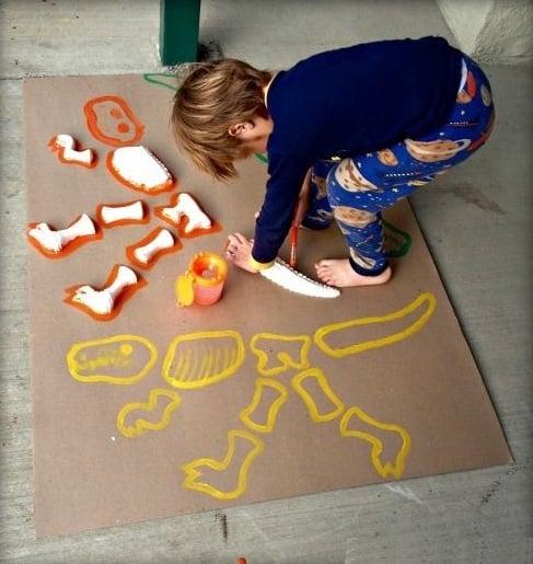 Niño descubriendo fosiles de dinosaurio hechos con papel