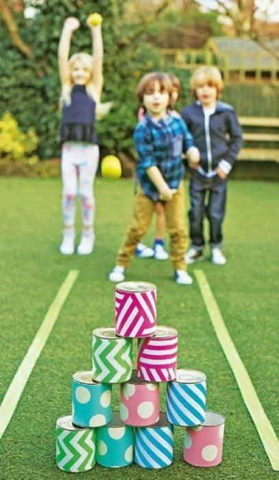 Niños jugando boliches con latas de colores