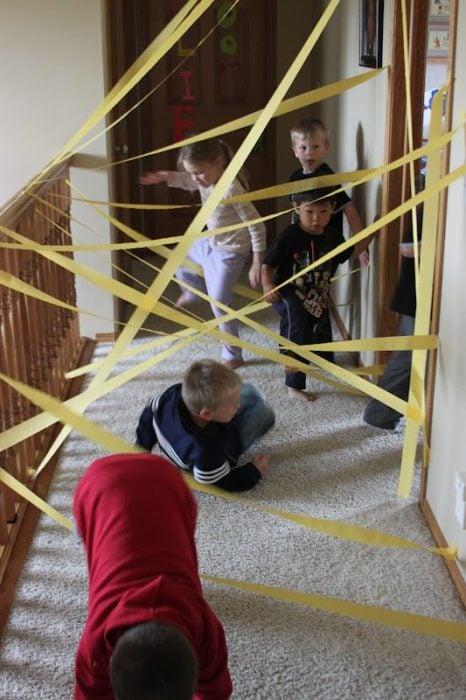 Niños jugando carrera de obstáculos con cintillas amarillas