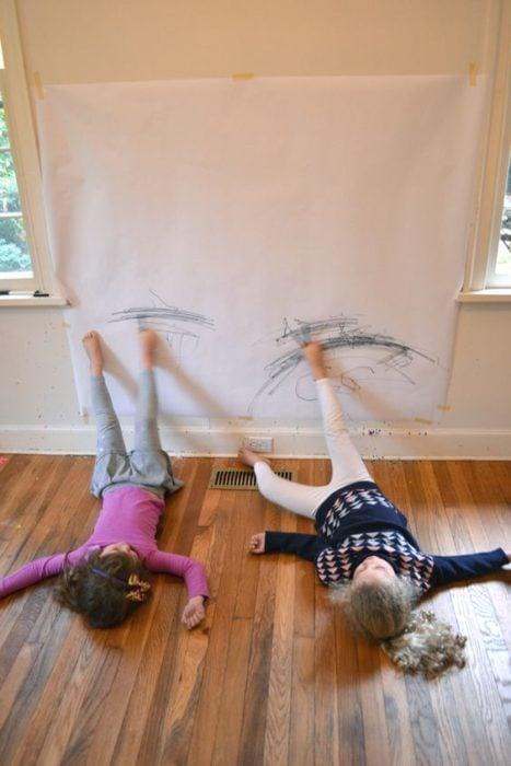 Niños dibujando con los pies sobre la pared