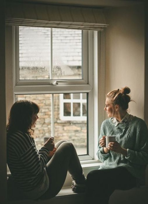 Par de amigas tomando café mientras platican