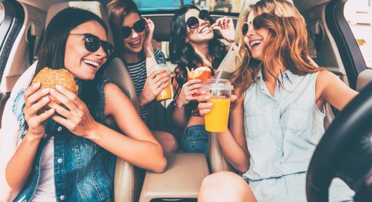 Chicas hablando en el auto mientras comen algo
