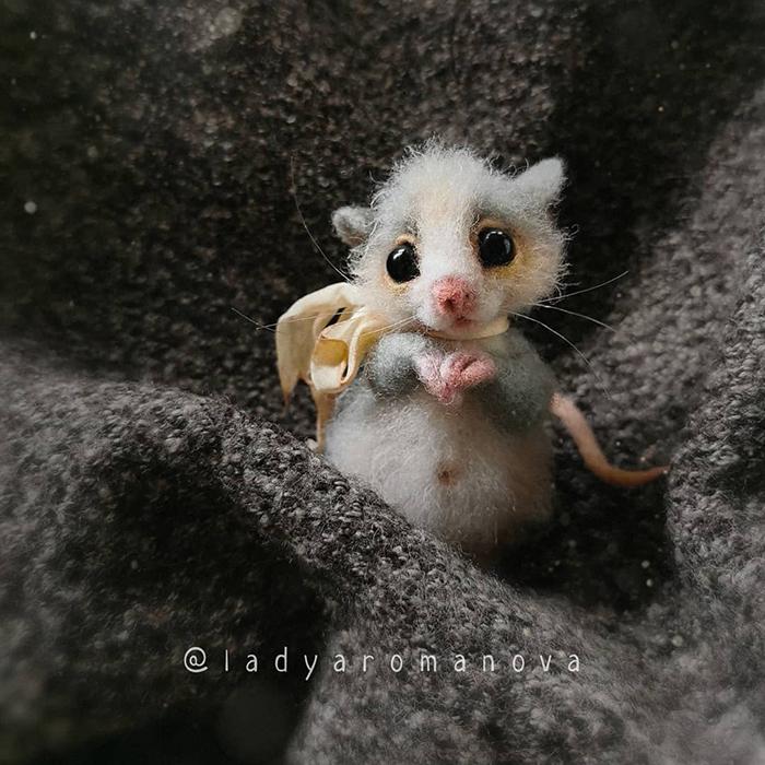 Figura de fieltro creada por la artista rusa Anna Romanova, ratoncito gris comiendo queso
