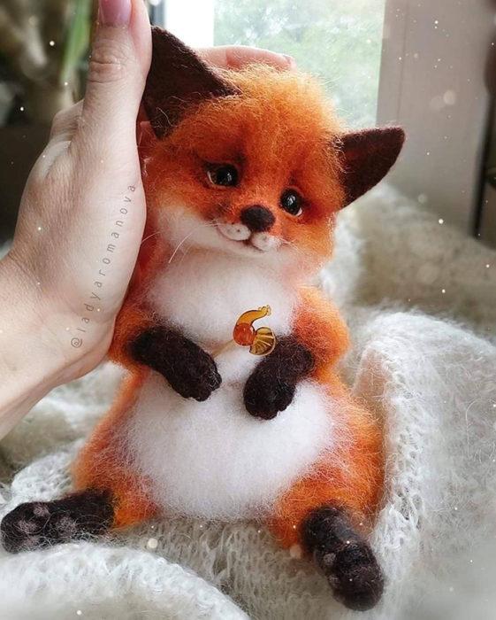 Figura de fieltro creada por la artista rusa Anna Romanova zorro naranja recostado en una cobija blanca