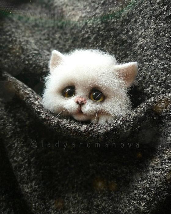 Figura de fieltro creada por la artista rusa Anna Romanova gato blanco dentro de un saco gris