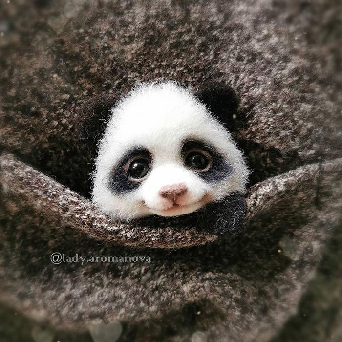 Figura de fieltro creada por la artista rusa Anna Romanova panda pequeño dentro de un saco gris