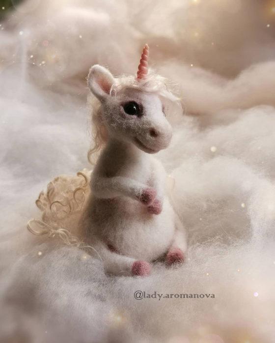 Figura de fieltro creada por la artista rusa Anna Romanova unicornio sentado sobre fieltro blanco