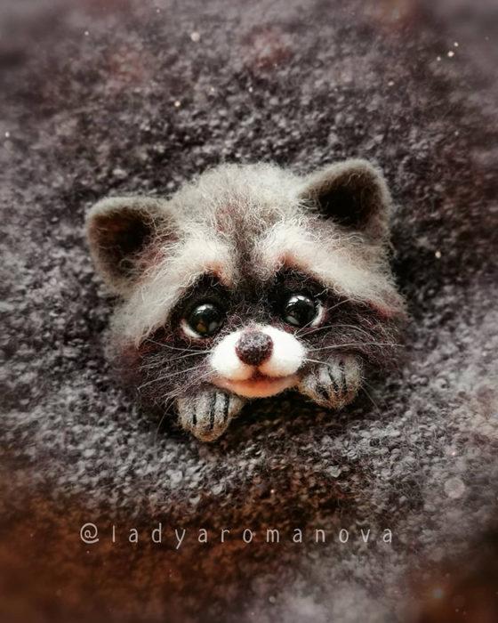 Figura de fieltro creada por la artista rusa Anna Romanova mapache dentro de un saco gris
