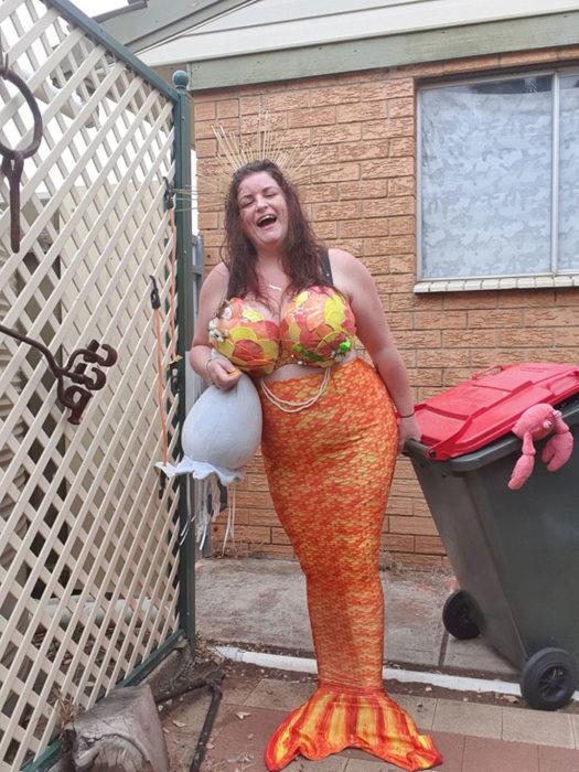 Mujer vestida como sirena lista para sacar la basura