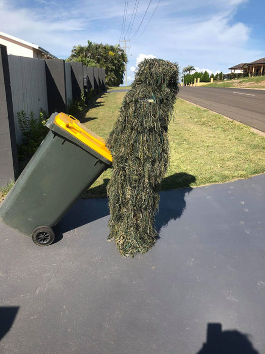 Persona usando un disfraz de camuflaje para sacar la basura