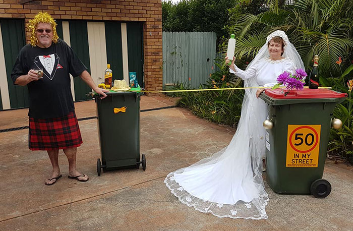 Pareja usando sus trajes de boda para sacar la basura en Australia