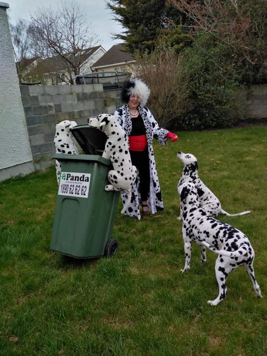 Mujer vestida de Cruella DeVil sacando la basura fuera de su casa