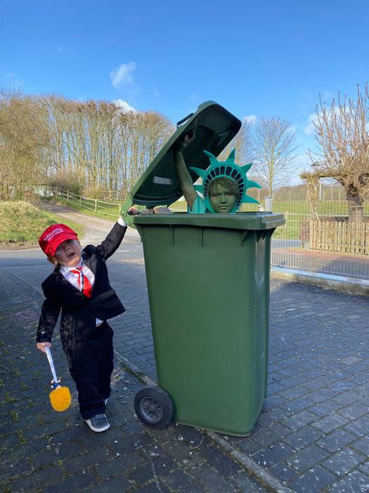 Señora disfrazada de estatua de la libertad dentro de un contenedor de basura