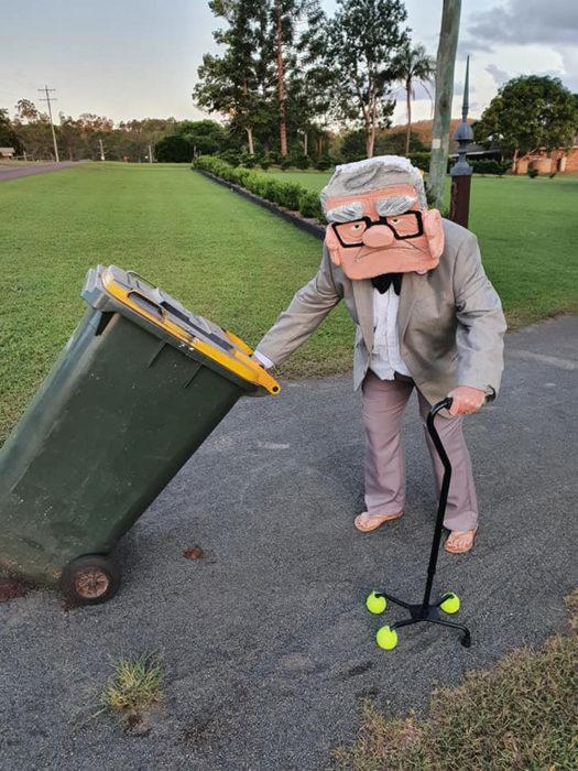 Señor disfrazado de anciano de Up mientras saca la basura