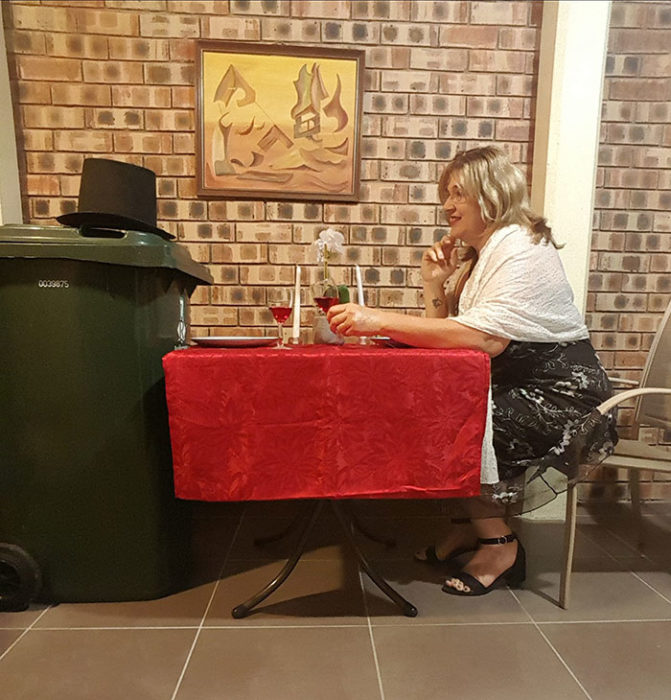 Señora vistiendo un vestido mientras simula una cena con el bote de basura de su casa