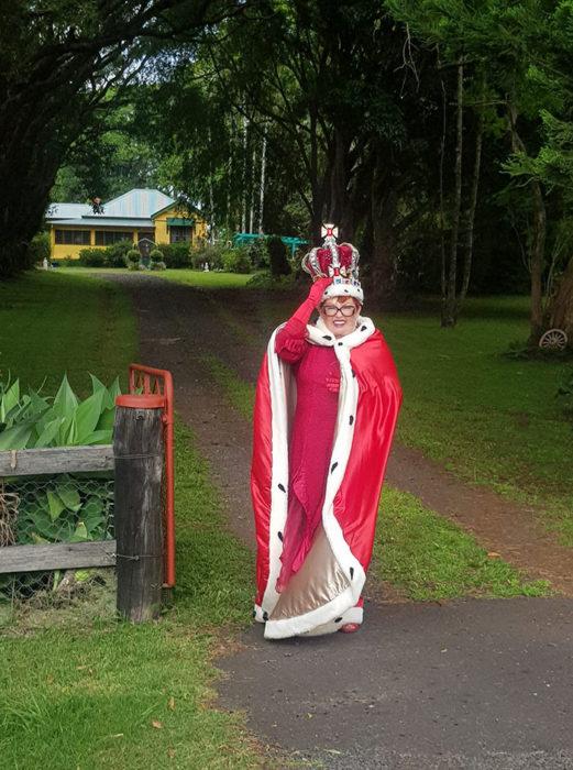 Señora vestida de reina con un traje rojo con capa