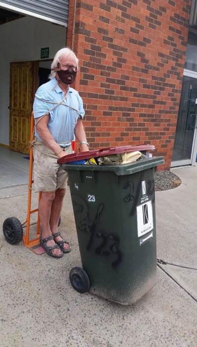 Señor disfrazado de hanibal lecter mientras saca la basura de su casa