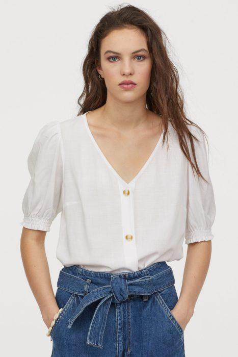 Chica utilizando blusa blanca con mangas abombadas de la colección