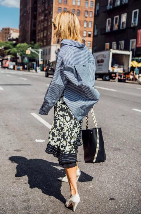 Atuendos con tu boyfriend shirt, camisa de tu novio, blusa oversized azul con rayas, falda con ornamentos, tacones blancos, mujer rubia caminando en la calle