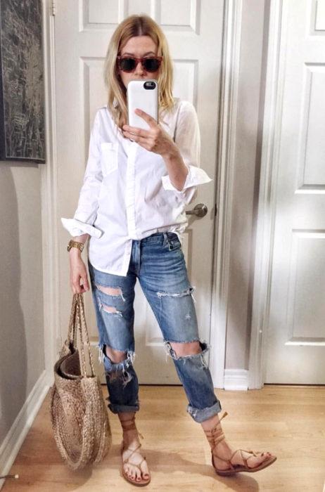 Atuendos con tu boyfriend shirt, camisa de tu novio, blusa oversized blanca, fajada a la mitad, con sandalias de gladiador, mujer tomándose selfie frente al espejo