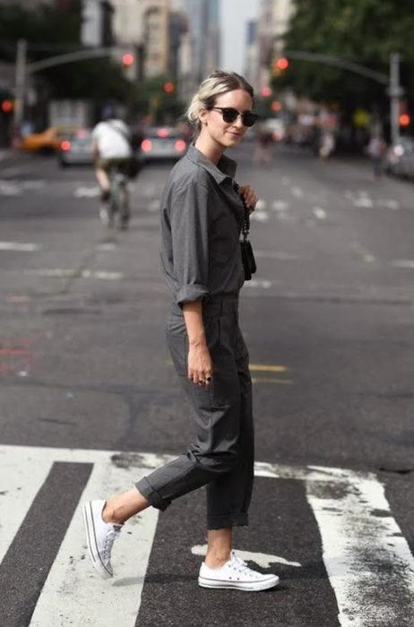 Atuendos con tu boyfriend shirt, camisa de tu novio, blusa oversized gris, mujer cruzando la calle con lentes y pantalón de trabajo, oficina, tenis blancos converse