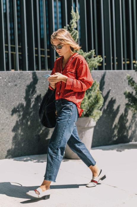 Atuendos con tu boyfriend shirt, camisa de tu novio, blusa oversized roja, con mom jeans, flats con tacones, mujer mirando su celular mientras camina