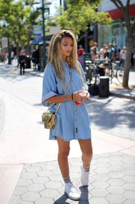 Atuendos con tu boyfriend shirt, camisa de tu novio, blusa oversized azul de mezclulla como vestido, con tenis blancos, mujer rubia en la calle