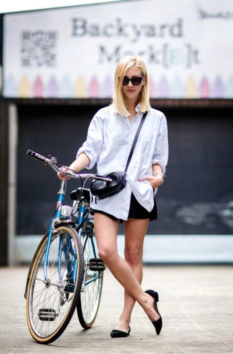 Atuendos con tu boyfriend shirt, camisa de tu novio, blusa oversized blanca, short negro, ballerinas, mujer rubia con bicicleta