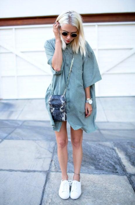 Atuendos con tu boyfriend shirt, camisa de tu novio, blusa oversized verde como vestido, con tenis blancos, mujer rubia en la calle con lentes de sol modernos y redondos