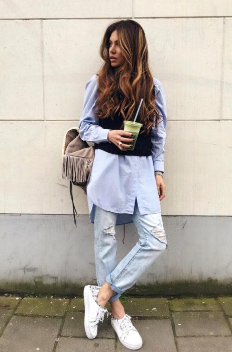 Atuendos con tu boyfriend shirt, camisa de tu novio, blusa oversized azul debajo de un chaleco negro, mom jeans desgastados y rotos, mujer de cabello ombré, largo, ondulado, recargada en la pared con un té matcha