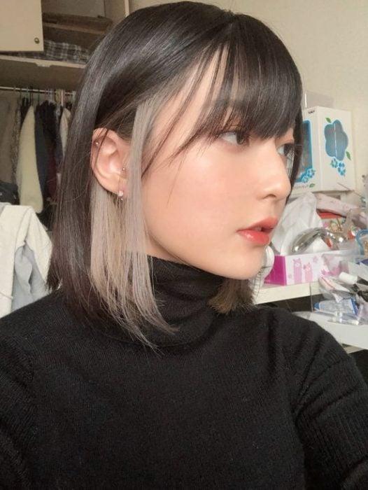 Chica de cabello corto lacio con un mechón blanco