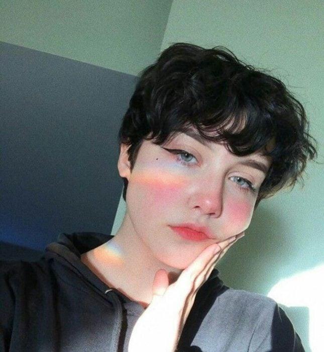 Chica con cabello muy corto ondulado con blusa negra
