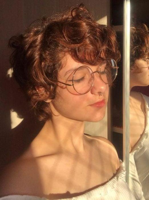 Chica pelirroja con cabello rizado y muy corto con lentes grandes redondos
