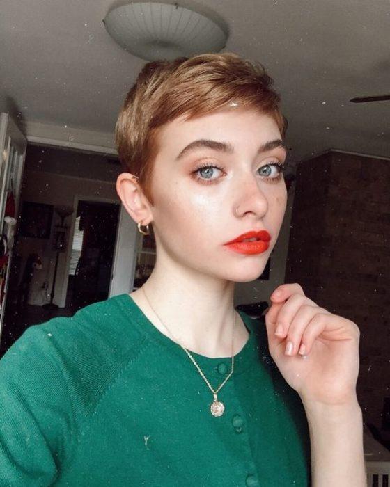 Chica rubia de ojos azules con cabello estilo piexie usa suéter verde