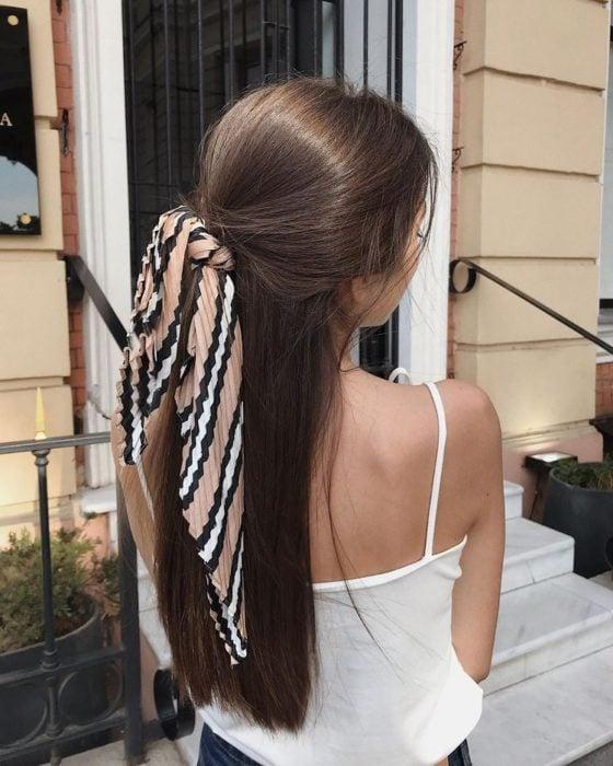 Chica de espaldas mostrando su peinado de media coleta con lazo, tiene cabello largo lacio