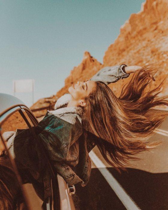 Chica en viaje en carretera asomandose por la ventana