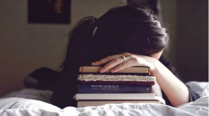 Chica cansada recargada sobre unos libros