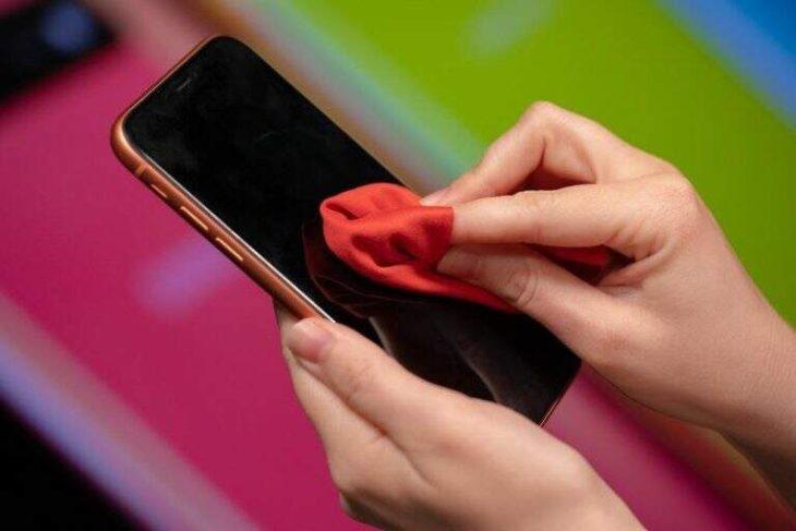 Persona limpiando pantalla del celular