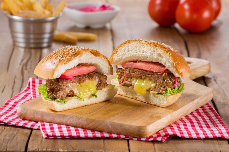 Hamburguesa rellena de queso amarillo con lechuga y tomate