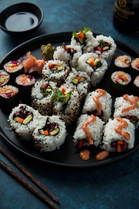 Suchi de pescado con aguacate en un plato negro amplio