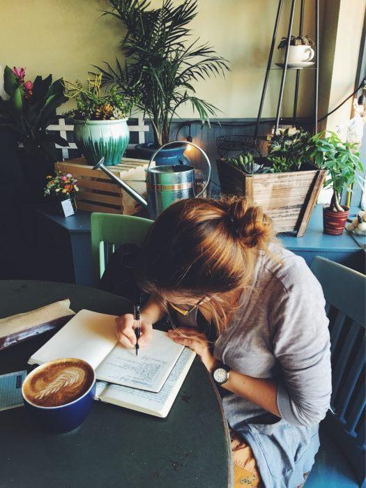 Chica escribiendo mientras toma café