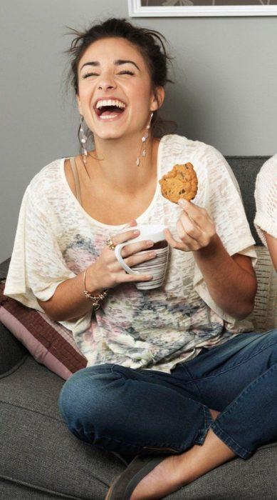 Chica riendo a arcajadas mientras come una galleta y toma un té