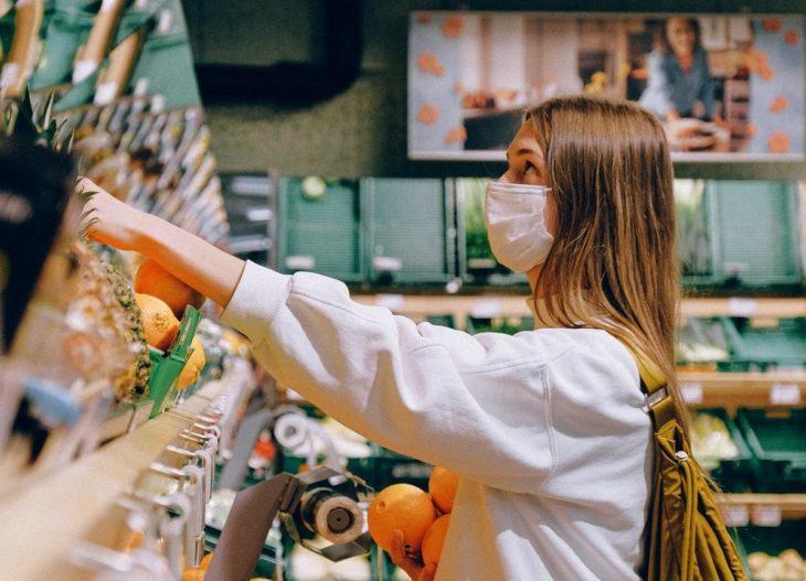 Chica comprando verduras en el supermercado