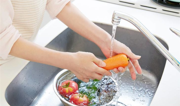 Mujer lavando frutas y verduras