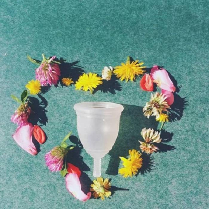 Copa menstrual rodeada por un corazón de flores